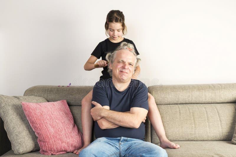 Menina que penteia e que faz a tranças seu paizinho em casa foto de stock