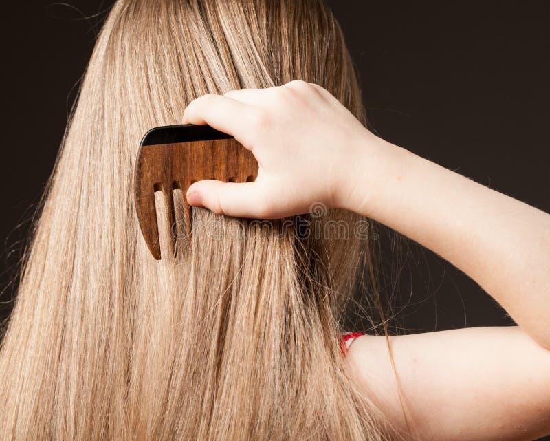Menina que penteia seu cabelo longo bonito fotografia de stock royalty free