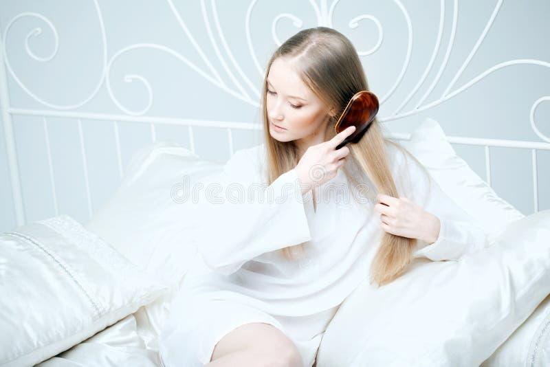 Menina que penteia seu cabelo na cama imagens de stock