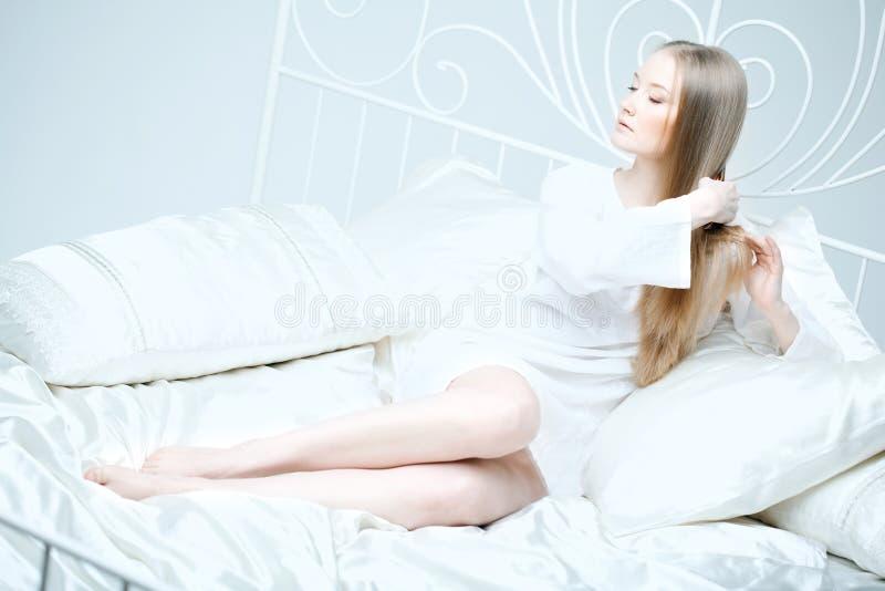 Menina que penteia seu cabelo na cama fotos de stock