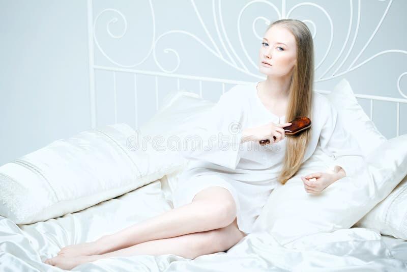 Menina que penteia seu cabelo na cama foto de stock