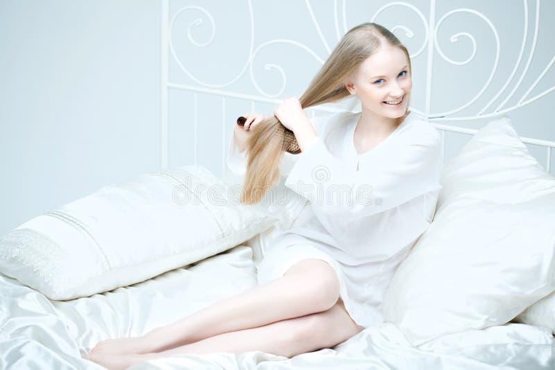 Menina que penteia seu cabelo na cama imagens de stock royalty free