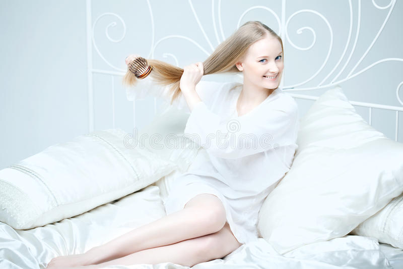Menina que penteia seu cabelo na cama imagem de stock