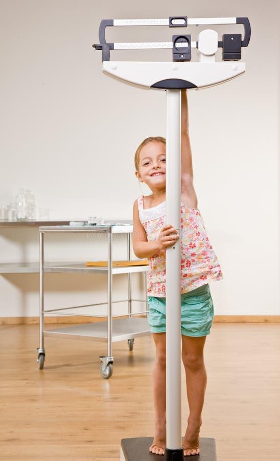 Menina que pesa-se no escritório do doutor fotografia de stock