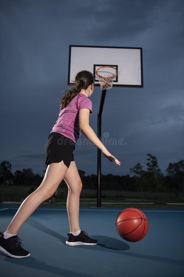 Menina que pinga um basquetebol em uma corte exterior fotografia de stock royalty free