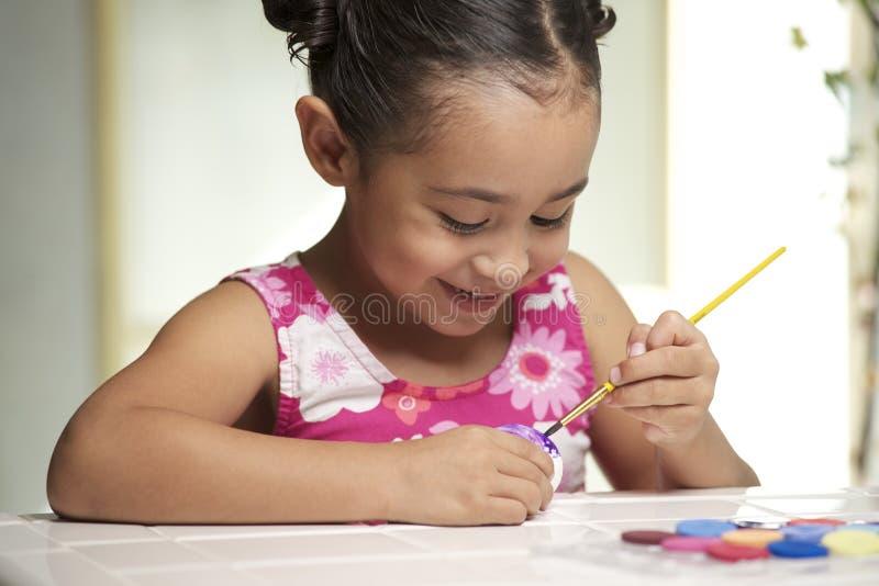 Menina que pinta um ovo de Easter imagens de stock royalty free