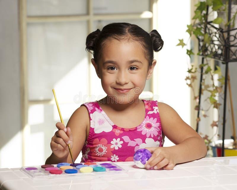 Menina que pinta um ovo de Easter fotos de stock royalty free