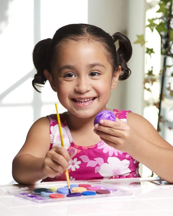 Menina que pinta um ovo de Easter imagens de stock
