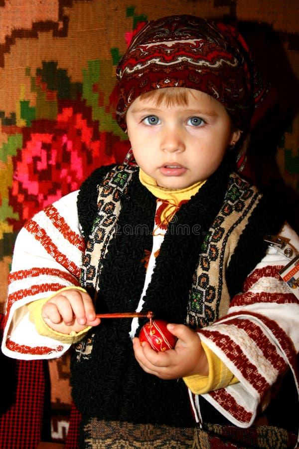 Menina que pinta um ovo em um acontecimento anual romeno fotos de stock