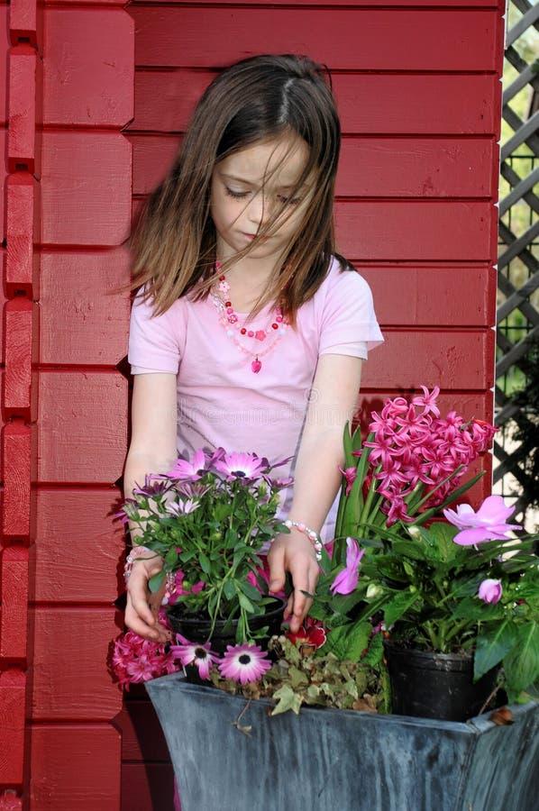 Menina que planta flores imagens de stock