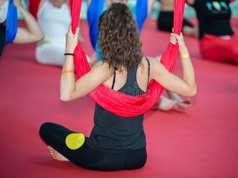 Menina que pratica a ioga macia: Assentado com pés e equilíbrio cruzados com uma tela elástica longa foto de stock royalty free