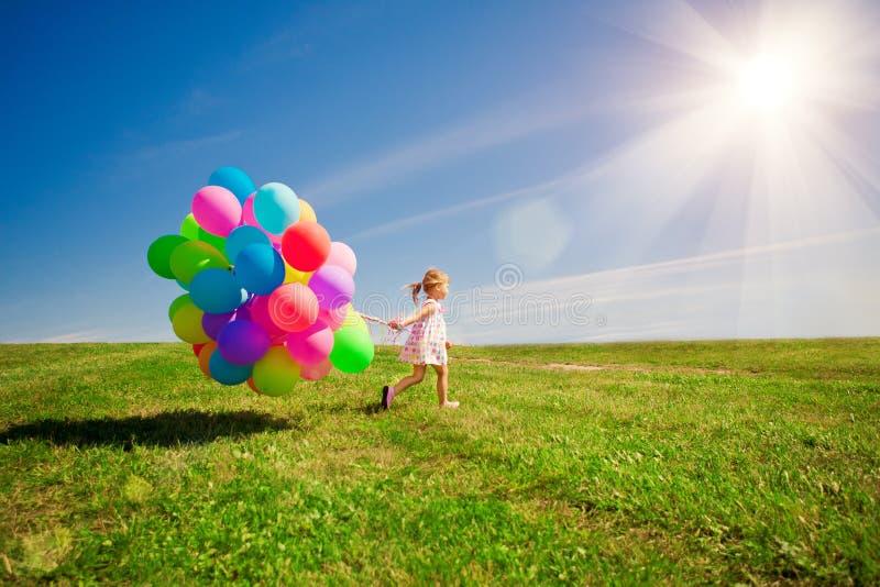 Menina que prende balões coloridos Criança que joga em um verde foto de stock