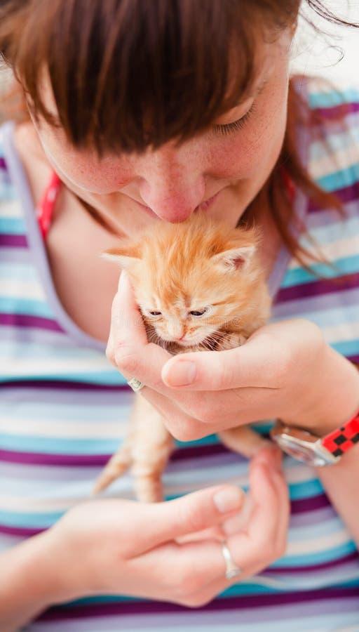 Menina que prende um gatinho vermelho foto de stock
