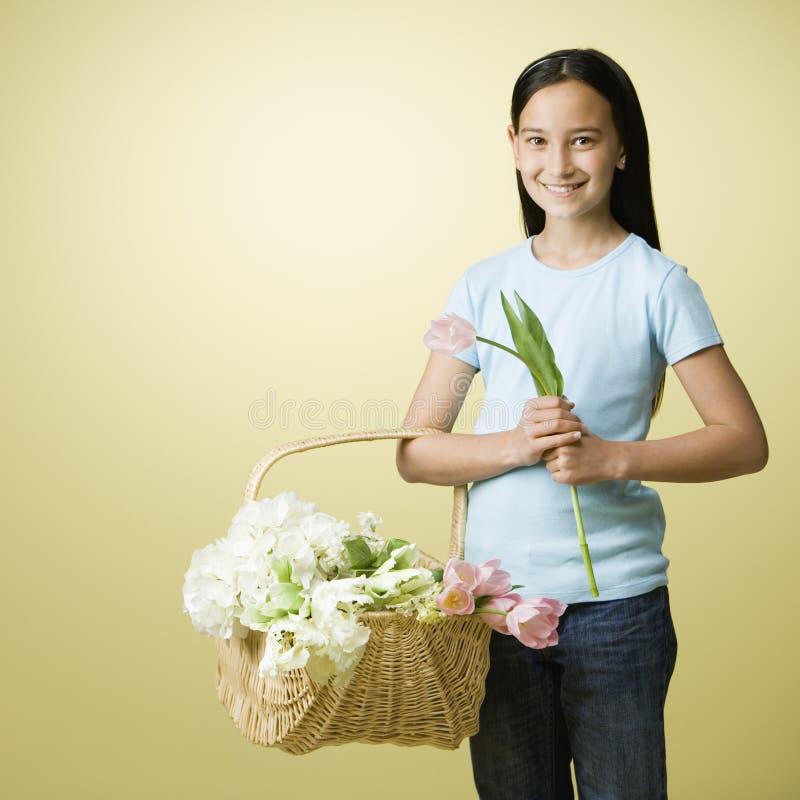 Menina que prende uma cesta do flowe foto de stock royalty free