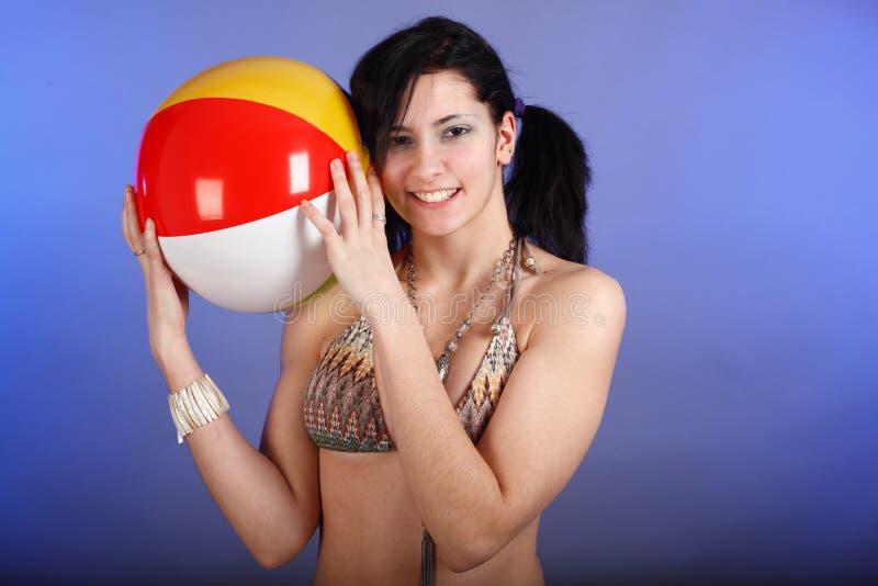 Menina que prende uma esfera de praia fotos de stock