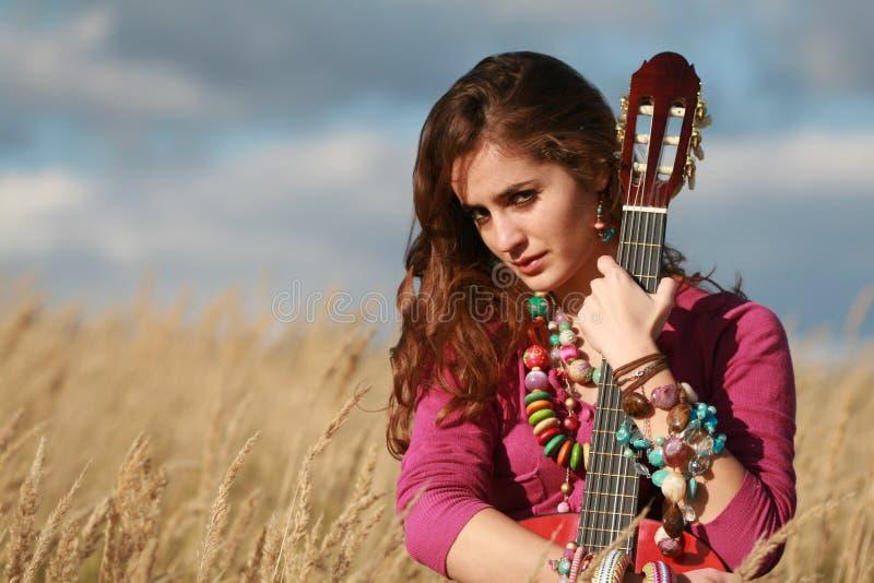 Menina que prende uma guitarra no campo imagens de stock