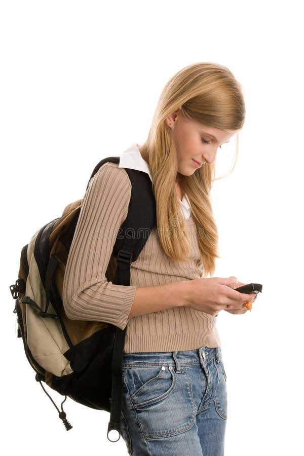 Menina que prepara-se à escola usando o telefone de pilha fotos de stock