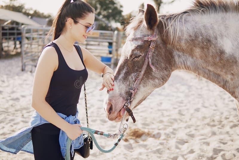 Menina que prepara-se para montar um cavalo fotografia de stock
