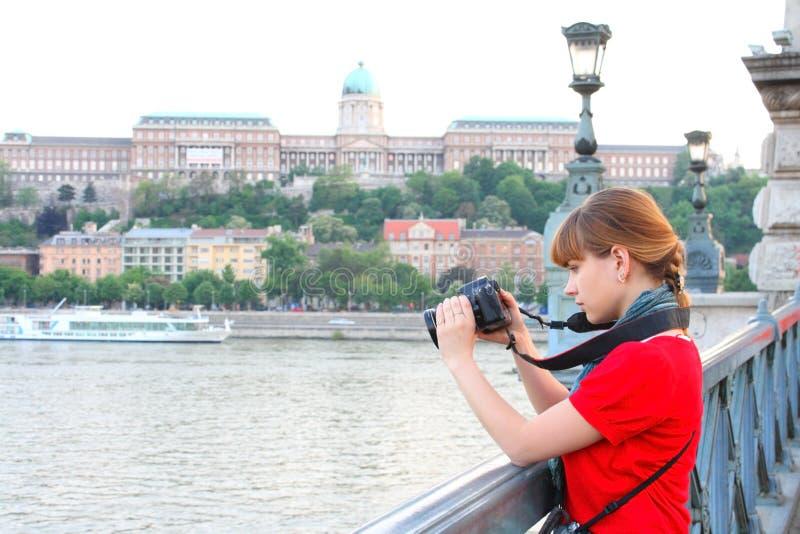 Menina que presta atenção no tiro na câmera de DSLR foto de stock