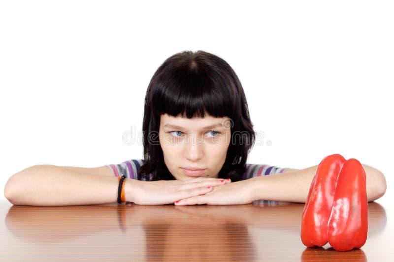 Menina que presta atenção a uma pimenta vermelha fotos de stock