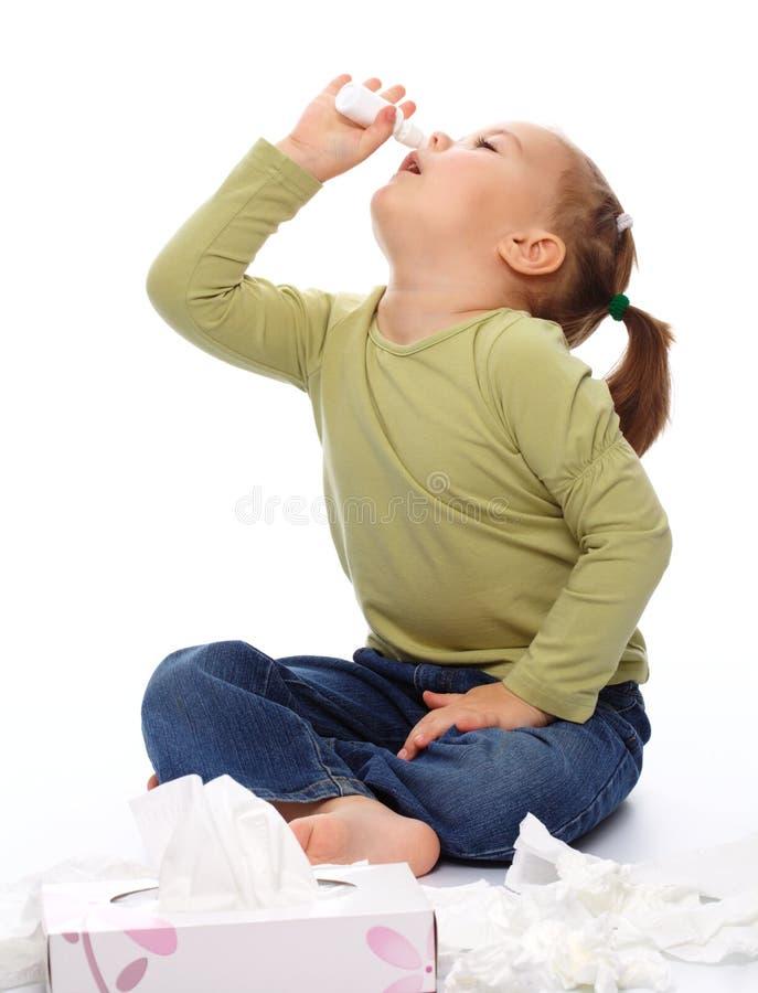 Menina que pulveriza seu nariz fotos de stock