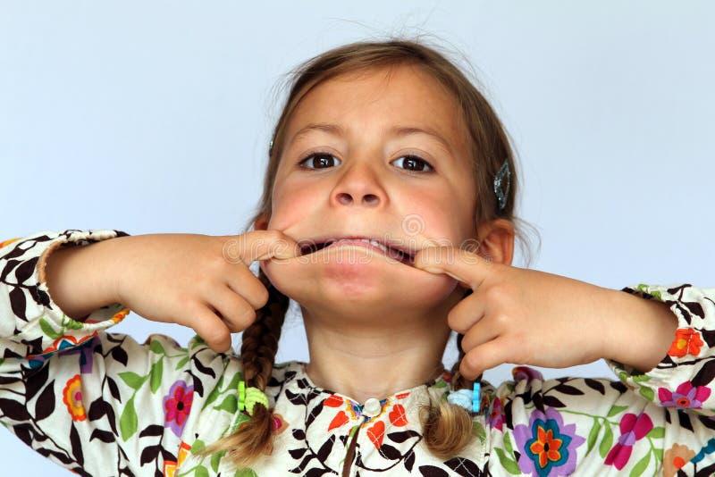 Menina que puxa uma face parva imagens de stock royalty free