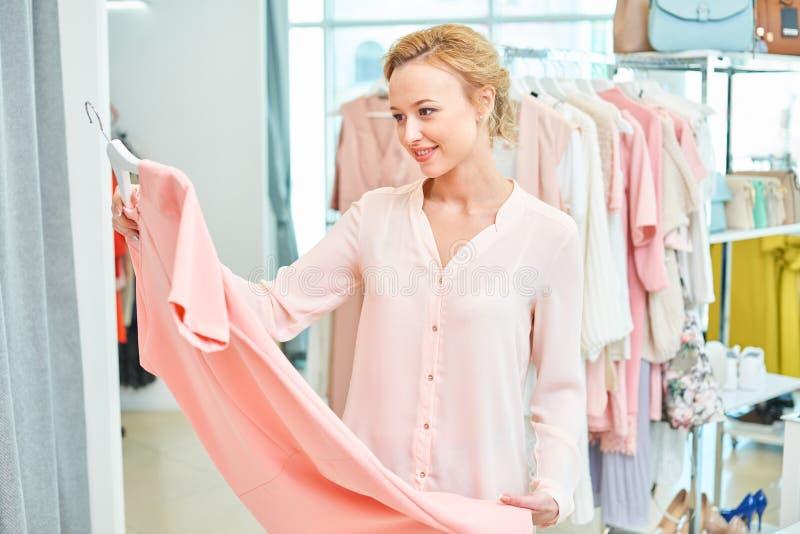 Menina que realiza em uma loja de roupa fotografia de stock royalty free