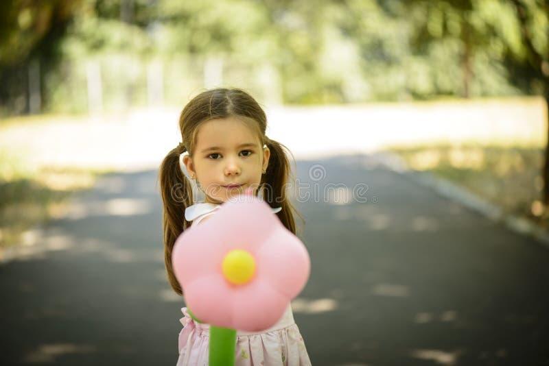 Menina que realiza o balão da forma da flor fora no parque do verão foto de stock