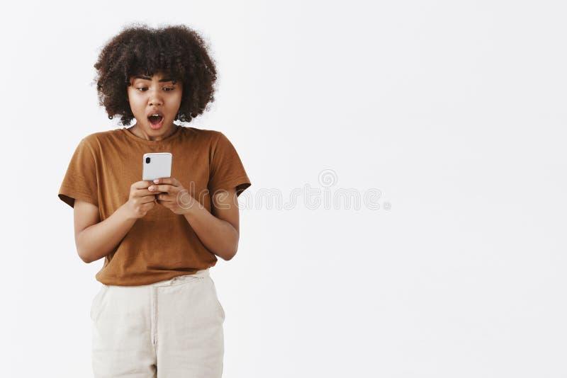 Menina que recebe más notícias através da mensagem Mulher adolescente afro-americano desagradada e chocada chocado com cabelo enc fotos de stock royalty free
