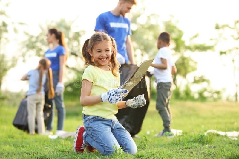 Menina que recolhe o lixo no parque imagens de stock