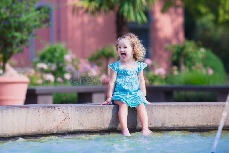 Menina que refresca em uma fonte fotos de stock