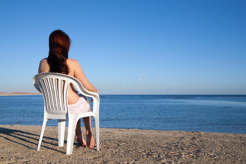 Menina que relaxa na praia do recurso imagem de stock