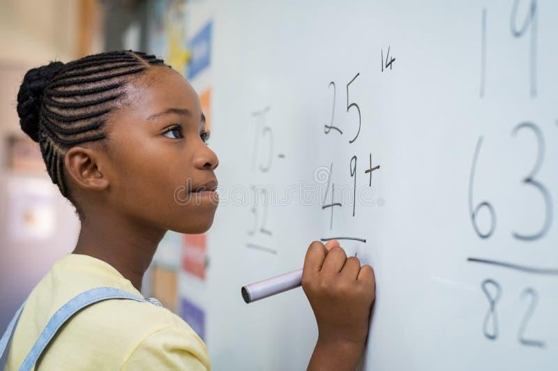 Menina que resolve a adição matemática fotos de stock