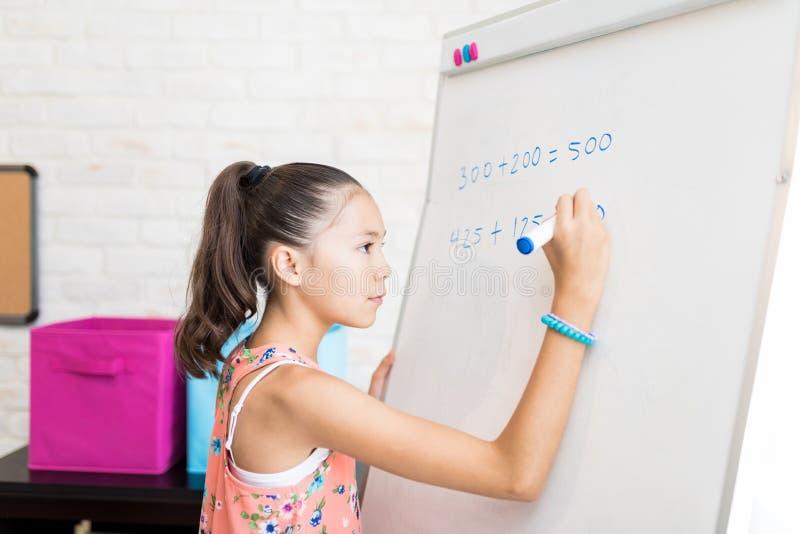 Menina que resolve somas do ` s da matemática em Flip Chart At Home imagem de stock royalty free