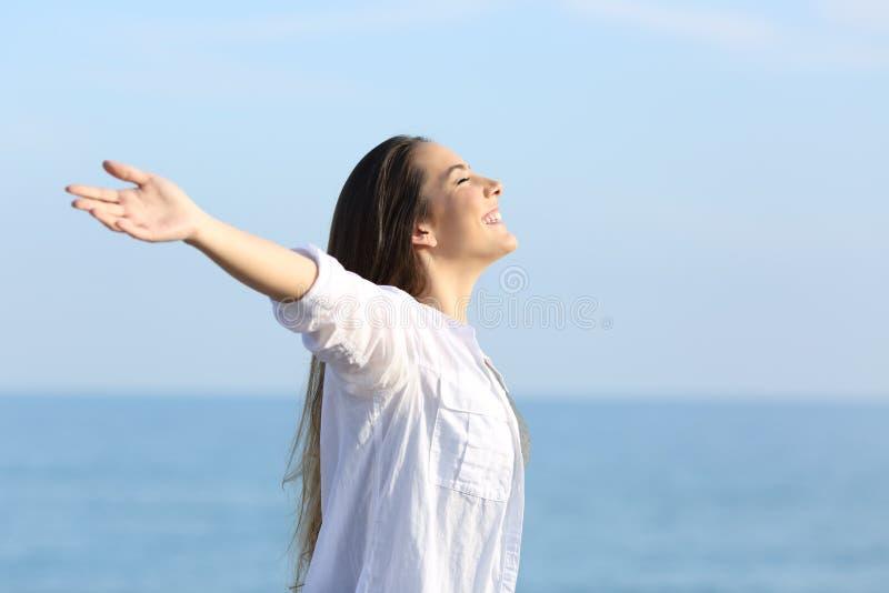 Menina que respira o ar fresco nos braços outstretching da praia imagens de stock royalty free
