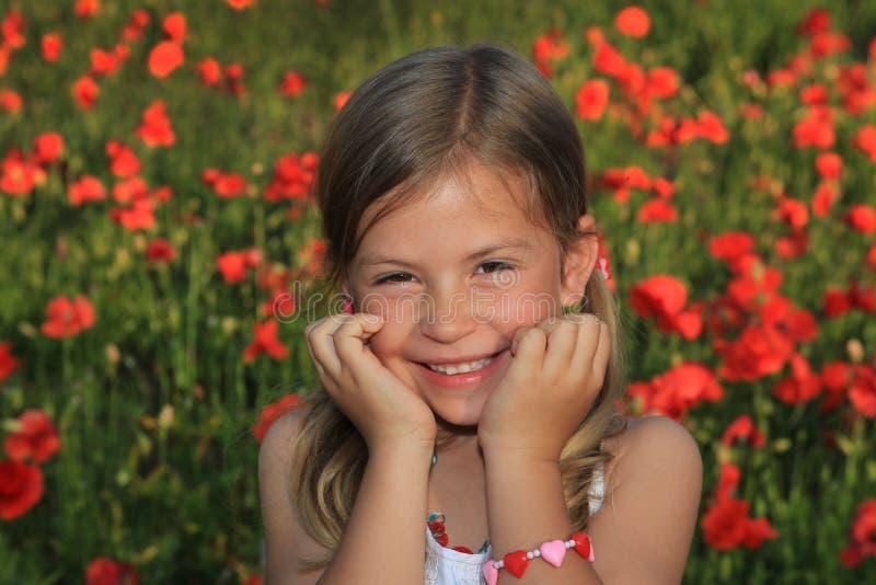 Menina que ri em um campo da papoila imagens de stock