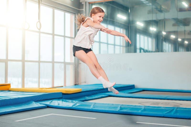 A menina que salta altamente em calças justas listradas no trampolim fotografia de stock
