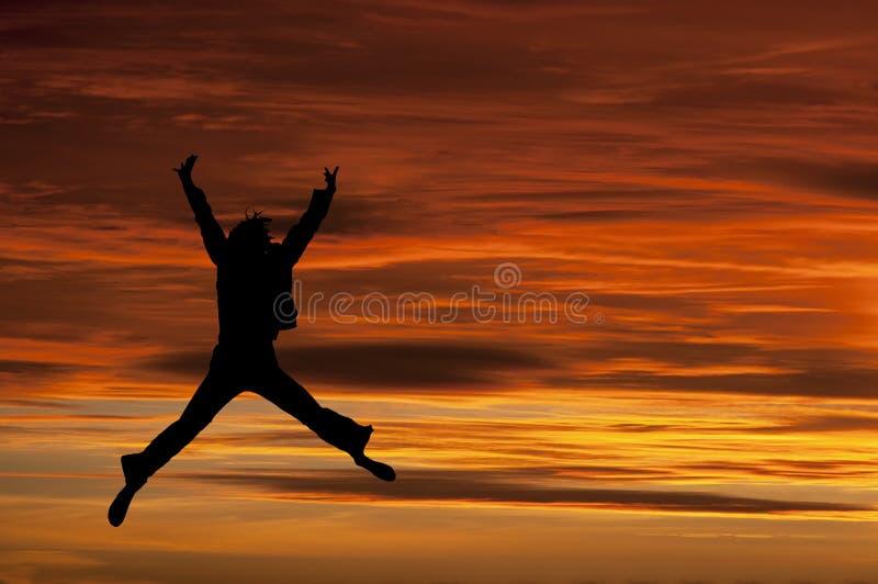 A menina que salta com alegria no por do sol ilustração stock