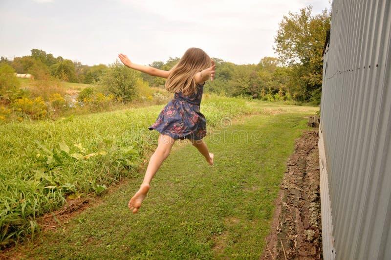 A menina que salta com pés desencapados foto de stock royalty free