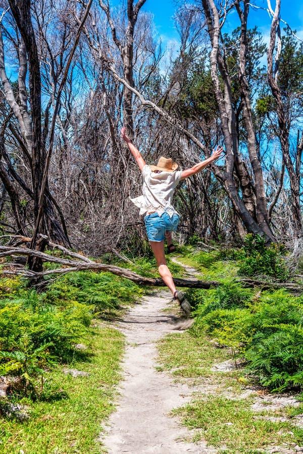 Menina que salta fora sobre a árvore caída através da trilha imagem de stock royalty free