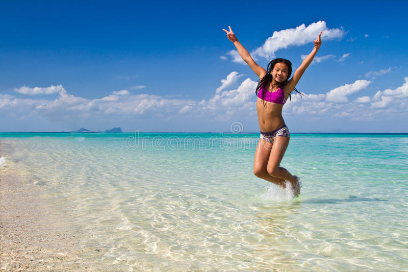 A menina que salta na água na praia imagens de stock