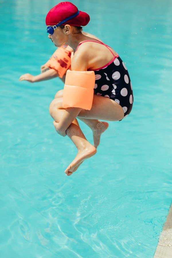 A menina que salta na piscina imagem de stock royalty free