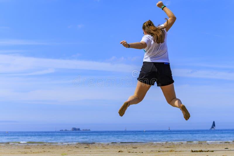 A menina que salta na praia imagem de stock