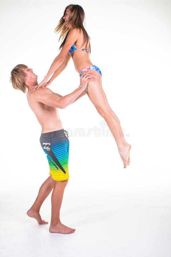 A menina que salta no homem novo arma-se com sua roupa da natação imagem de stock royalty free