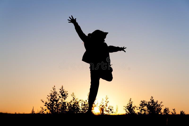 A menina que salta no por do sol imagens de stock