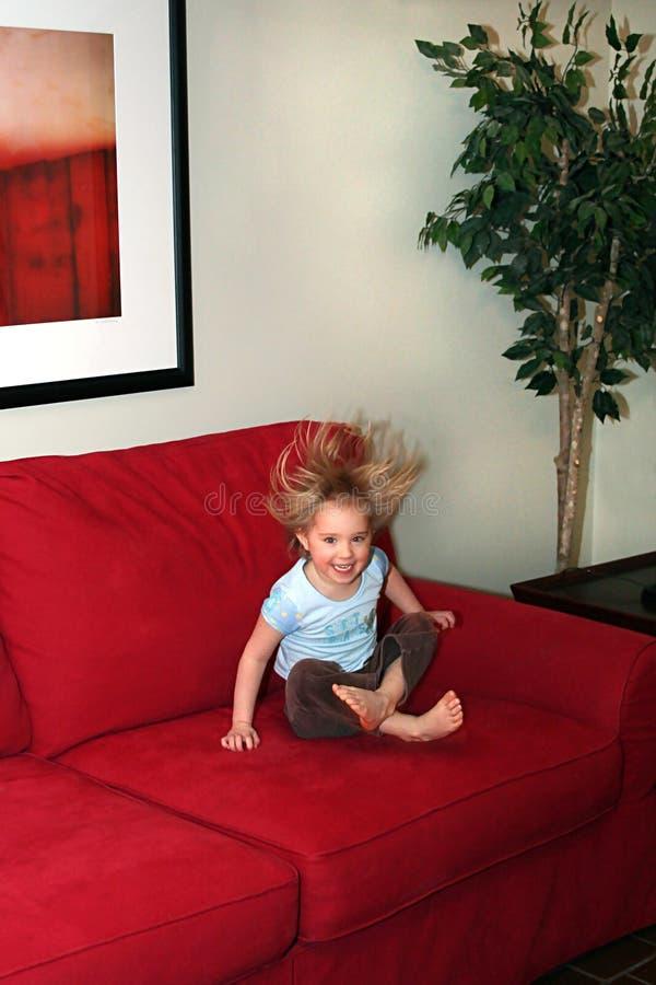 A menina que salta no sofá fotografia de stock