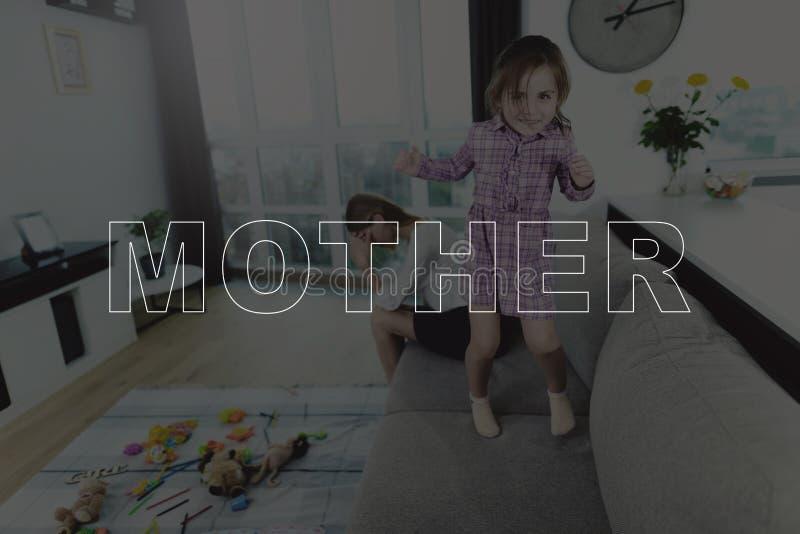 A menina que salta no sofá perto de sua mãe imagens de stock