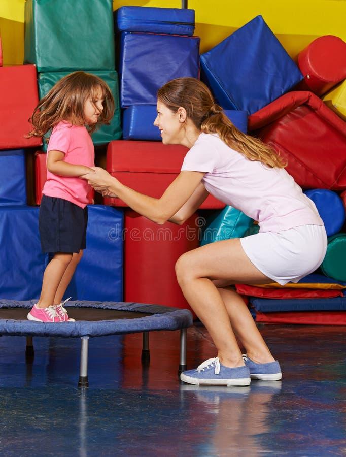 A menina que salta no trampolim fotografia de stock
