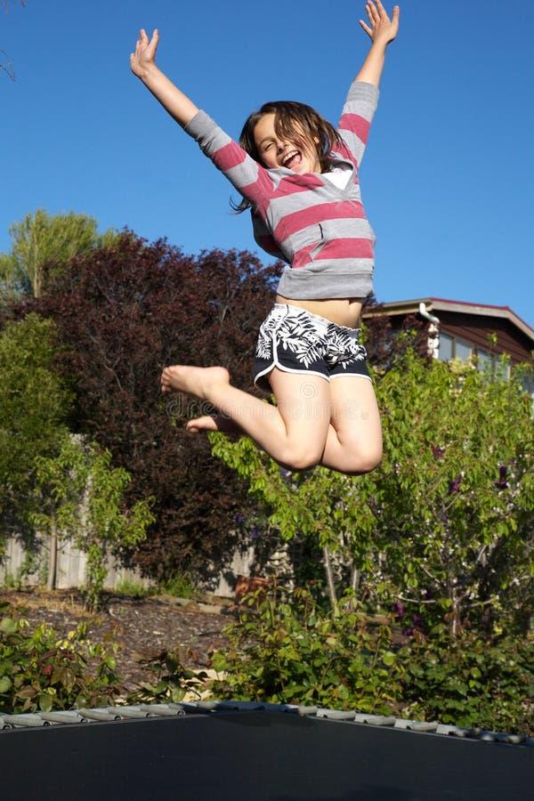 A menina que salta para a alegria no trampoline fotografia de stock