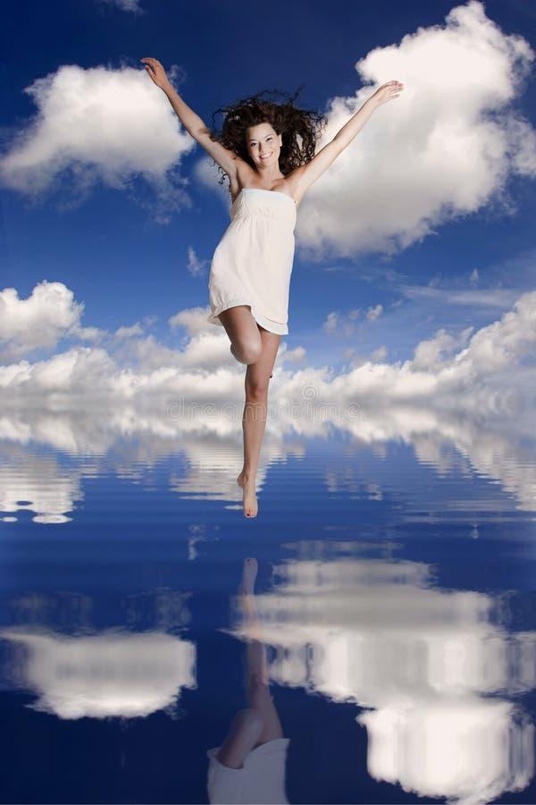 A menina que salta sobre a água imagens de stock royalty free